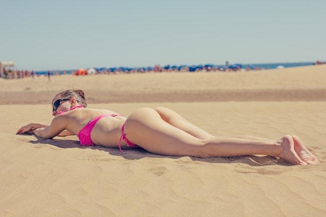 Žena v ružových plavkách, opaľújúca san a pláži.jpg