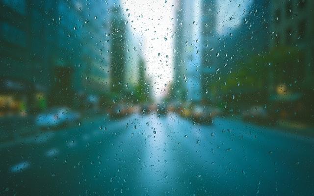 Pohľad na ulicu cez sklo s kvapkami vody.jpg