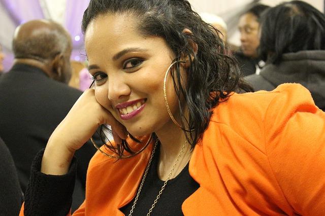Žena v oranžovom saku s veľkými kruhovými náušnicami.jpg