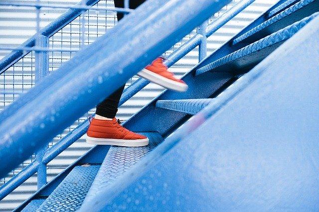 Človek kráča po kovových schodoch.jpg