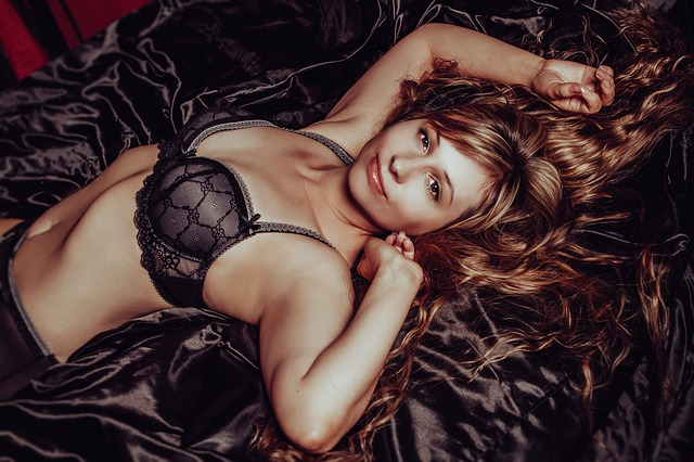 Žena v čiernej podprsenke na posteli.jpg