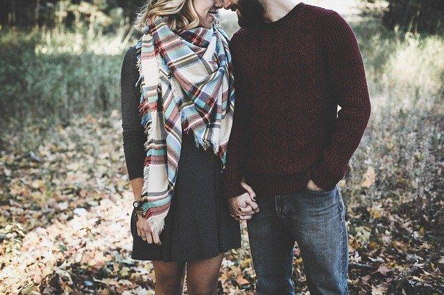 Muž a žena v lese sa držia za ruky