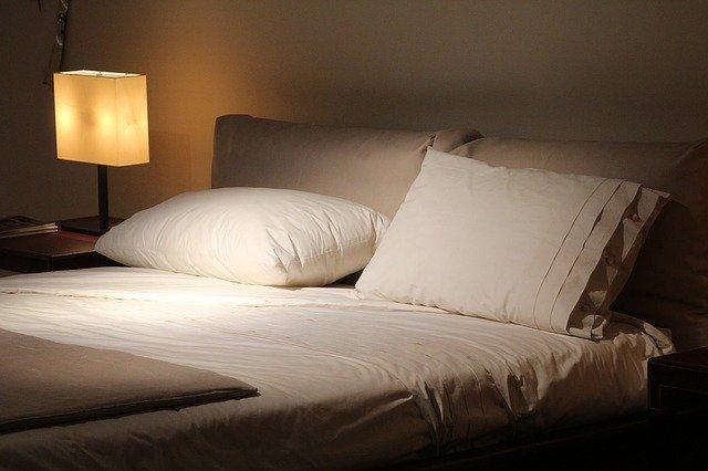 Manželská posteľ a nočný stolík so zapálenou lampou