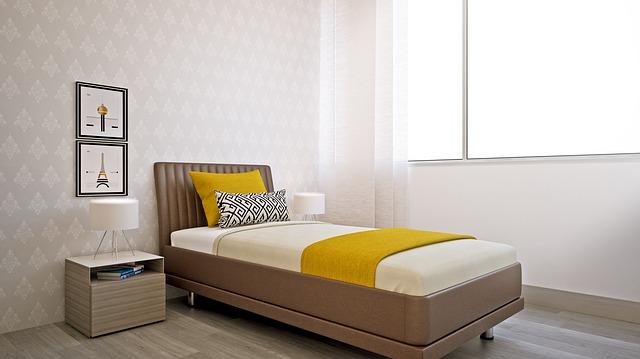 Úzka posteľ v izbe s tapetami na stenách