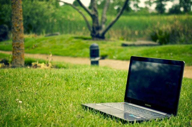 Notebook položený v zelenej tráve